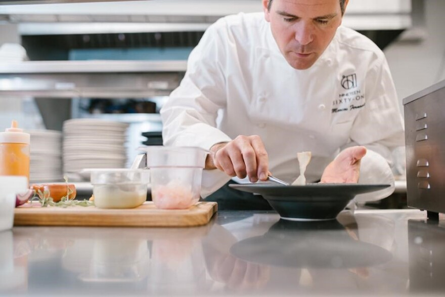 A chef finishes plating a dish.