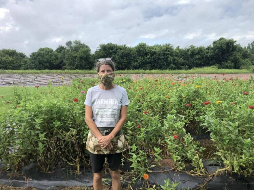 Katie Plohocky, executive director of the Healthy Community Store Initiative, stands in front of fields on Joe's Farm in Bixby, Oklahoma  on July 30. Plohocky helped salvage leftover crops on the farm last year when the nearby creek flooded.