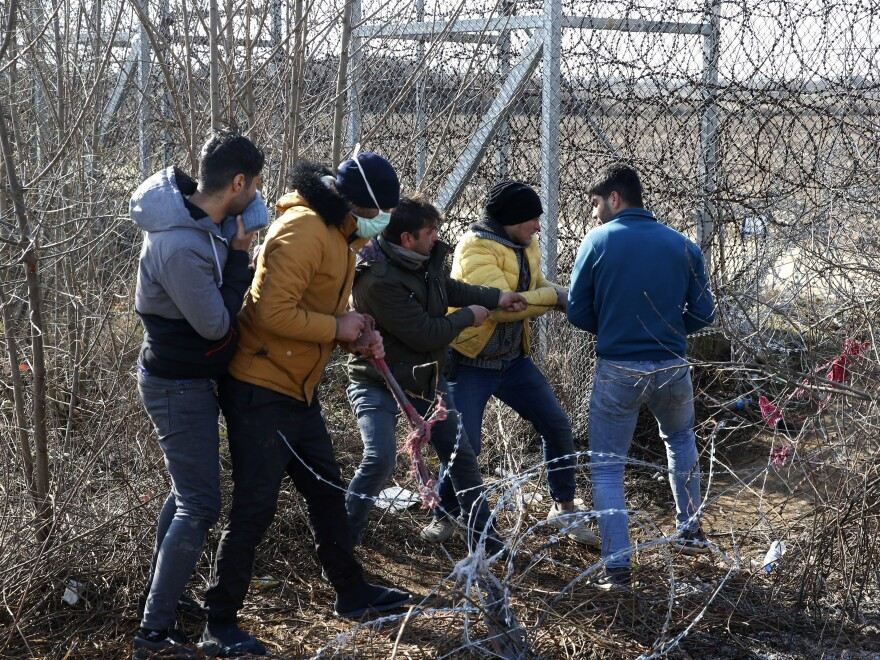 Migrants try to cut the fence at the Turkish-Greek border near the Pazarkule border gate in Edirne, Turkey, on Monday. Thousands of migrants and refugees massed at Turkey's western frontier, trying to enter Greece by land and sea after Turkey said its borders were open to those hoping to head to Europe.
