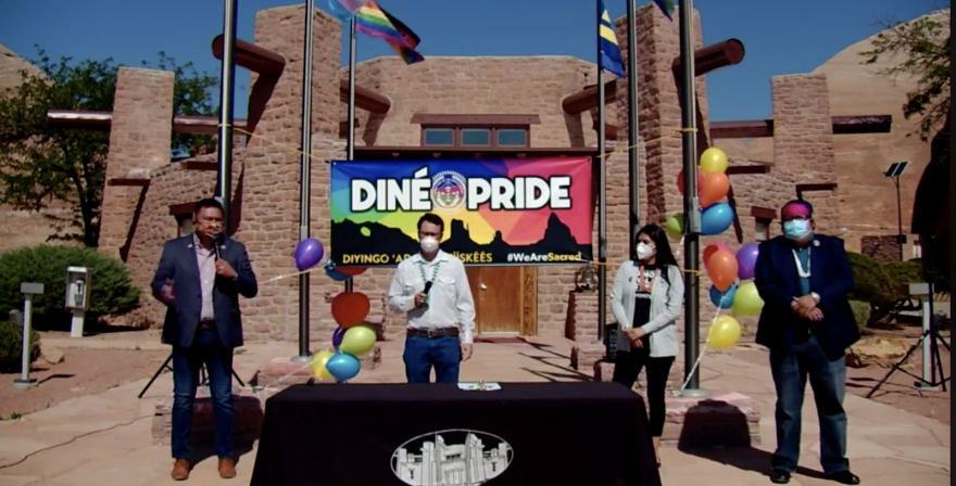 Four people stand in front of a sign that says Diné Pride.
