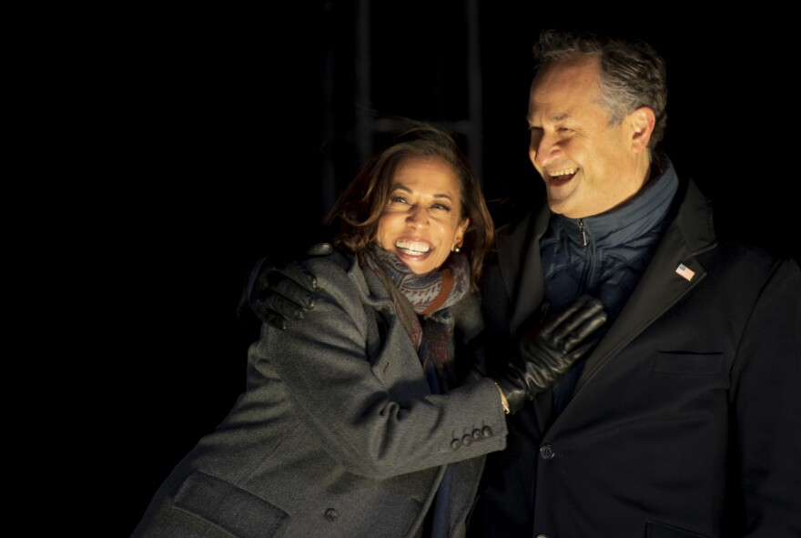 Sen. Kamala Harris and her husband, Doug Emhoff, embrace on stage at a drive-in election eve rally in Philadelphia.