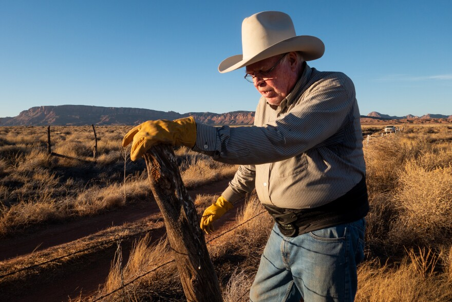 Against a background of buttes and dry grass, an elderly man in a cowboy hat adjusts a fence post and barbed wire.