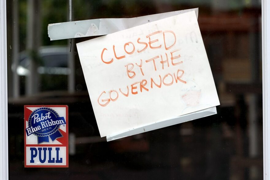 """A sign on a Houston bar reads """"Closed by the governor."""""""
