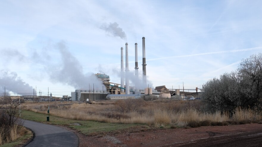 The stacks at the Colstrip coal-fired power plant emit white plumes against a blue sky
