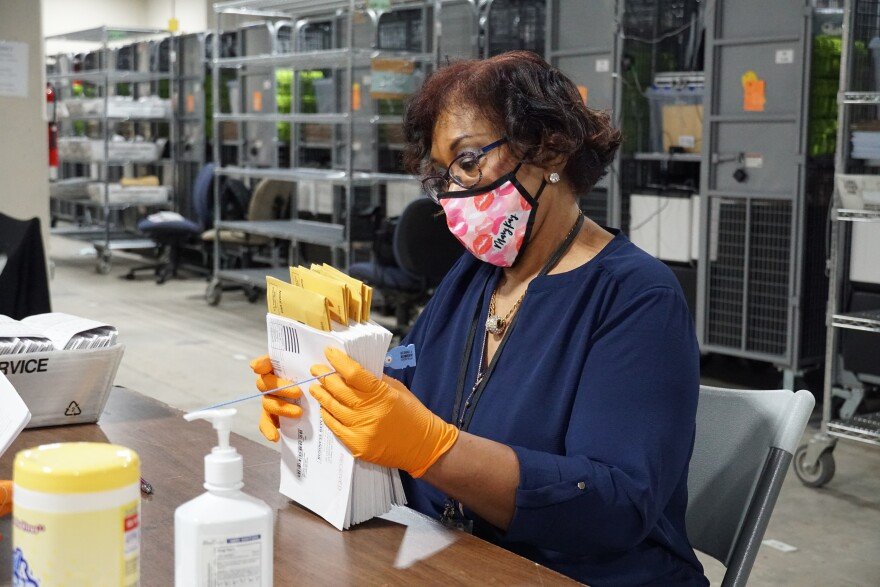 Colette Boyd finishes verifying a stack of absentee and mail-in ballots at the St. Louis County Board of Elections warehouse on July 30. 7/30/20