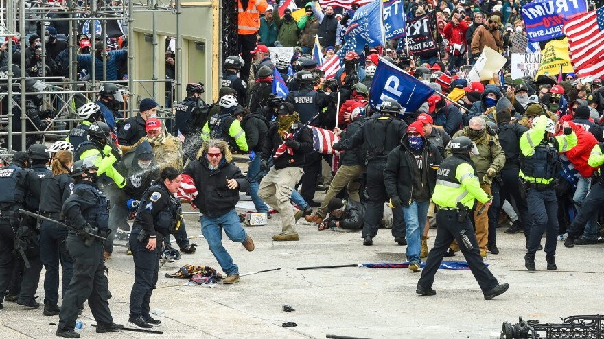 Trump supporters clash with police and security forces as they storm the Capitol earlier this month.