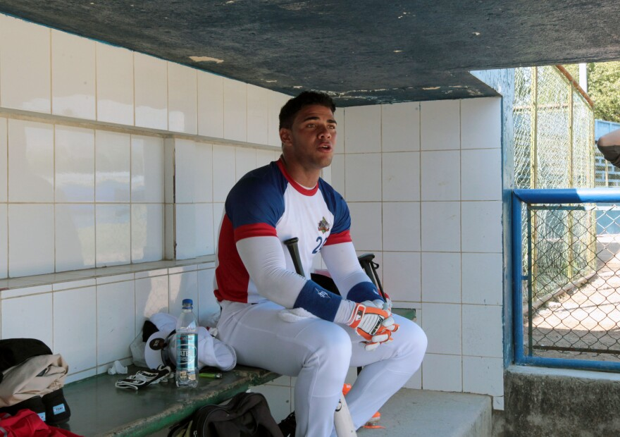 Cuban baseball player Yoan Moncada sits in the dugout before the start of an exhibition game for major league baseball scouts, in the Enrique Torrebiarte Stadium in Guatemala City in November.