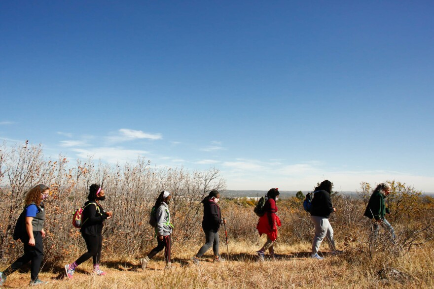 """(Left to right) Theresa Odello, Jessica Newton, Jan Garduno, Ashanta Cyprian, Joy Eloi and Jewyl Newton follow Lynn Wilson on a hike in a Colorado Springs park. Studies show """"if you are outdoors for at least five minutes, it literally brings your stress level down significantly,"""" says Newton."""