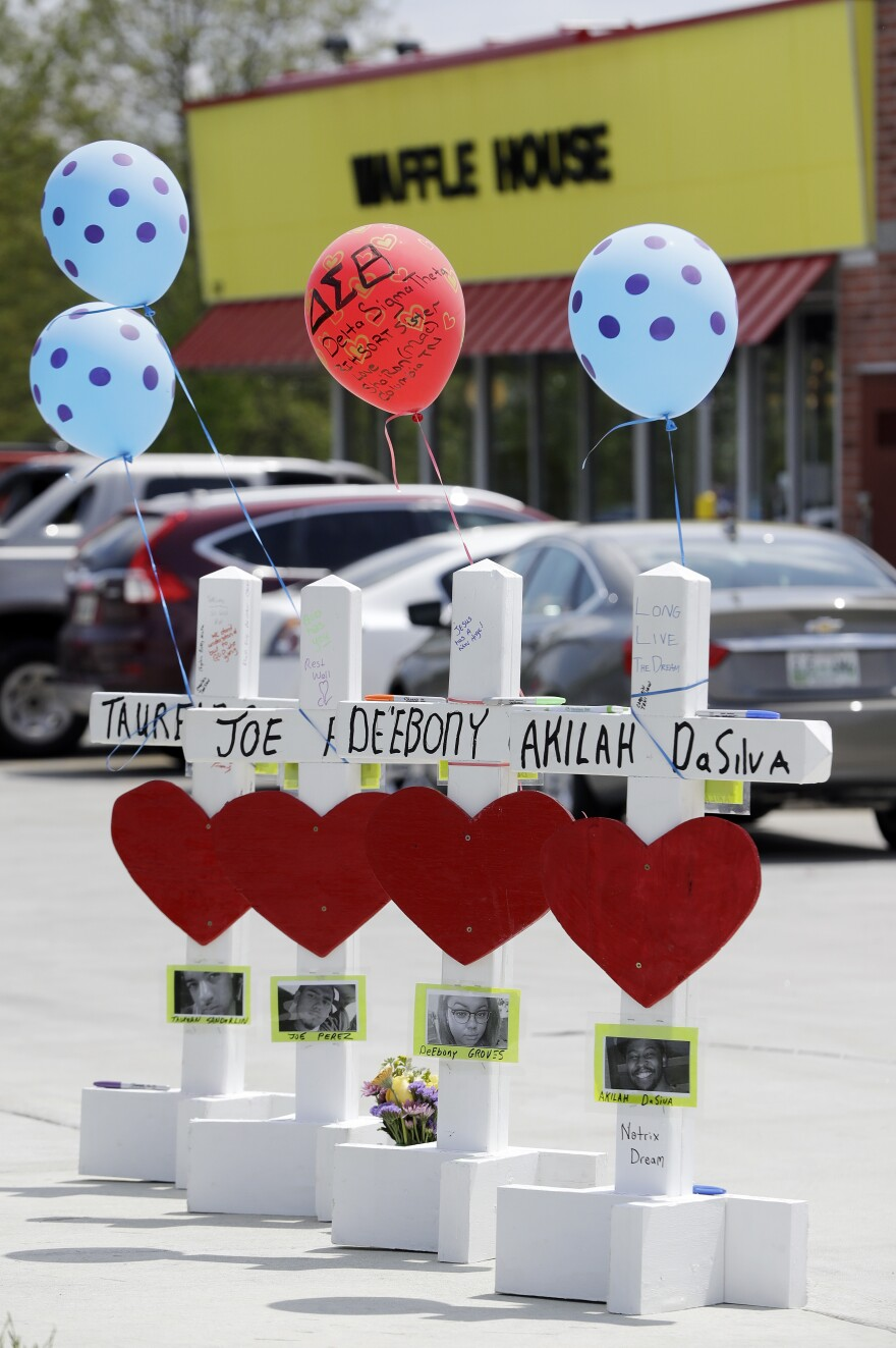 Four wooden crosses stand as a memorial Wednesday to those killed during a shooting at a Waffle House in Nashville, Tenn. The restaurant reopened three days after the attack.
