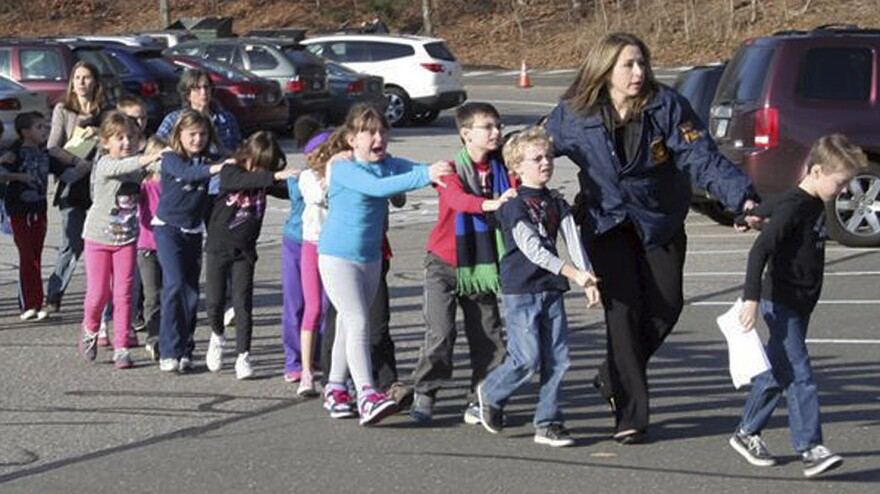 In a photograph taken by Shannon Hicks, police and teachers lead children away from Sandy Hook Elementary on Friday, Dec. 14.
