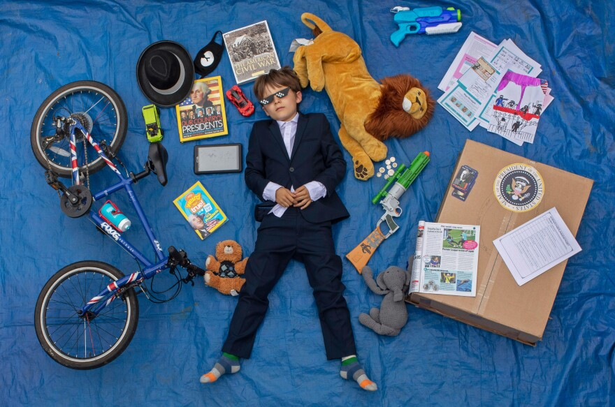 Ben, 10, lays next to his favorite objects, toys and books as part of a homeschooling assignment to create a time capsule to remind them of this time.