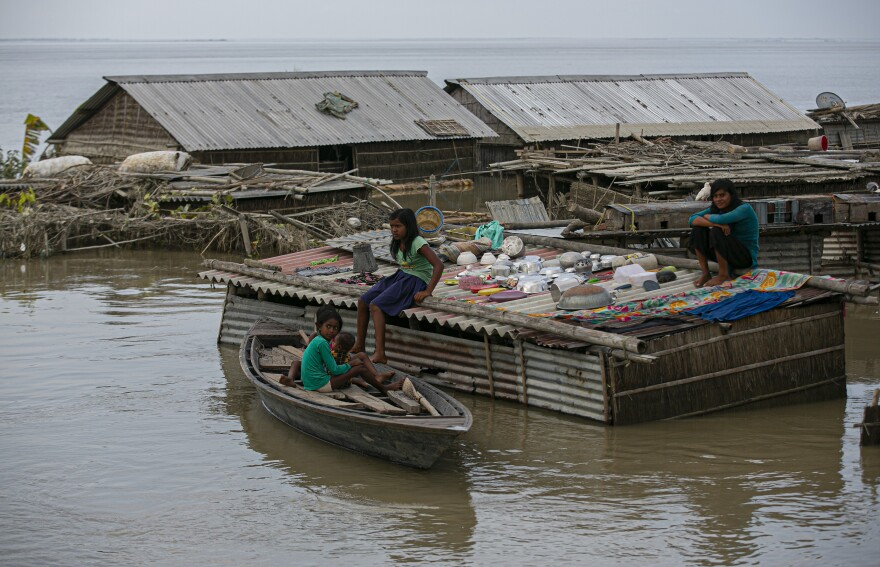 A family takes shelter on the roof of their house submerged in a flood along Brahmaputra river in Morigaon district, Assam, India, Thursday.