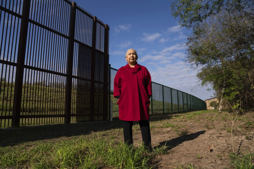 Juliet García, former president of the University of Texas at Brownsville, stands behind the border wall.