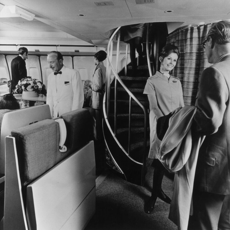 An air hostess greets a passenger in front of the spiral staircase leading to the upper deck lounge in a Boeing 747 in 1970.
