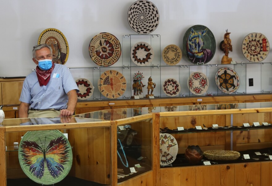 A man sits behind a counter with lots of baskets and weavings displayed around him.