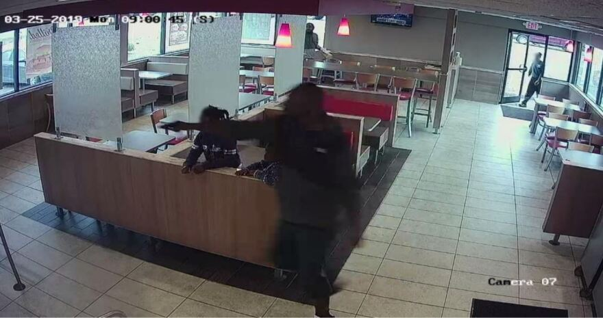 A video still from the DA's report. Danquirs Franklin points his gun, two of his children are in the background.