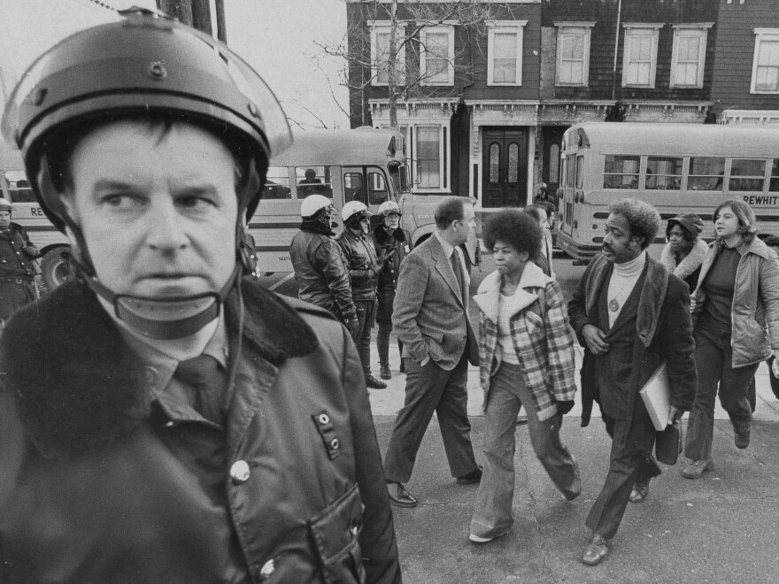 Buses arrive at South Boston High School, Jan. 8, 1975 as classes resume at the racially troubled institution. Police were on hand to provide protection as black students arrived.
