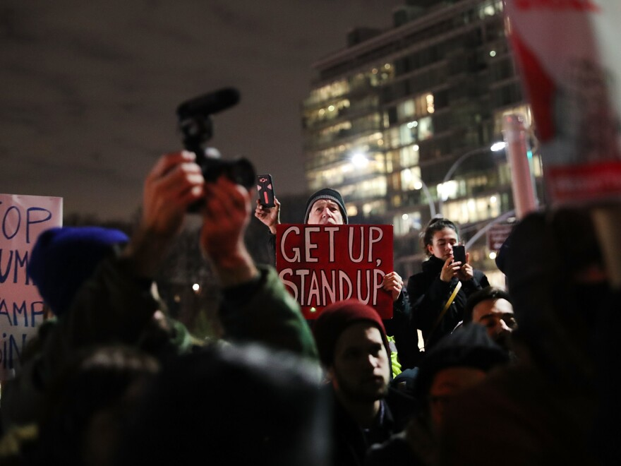Protesters attend a rally at Grand Army Plaza in Brooklyn before marching to Sen. Charles Schumer's apartment on Tuesday.