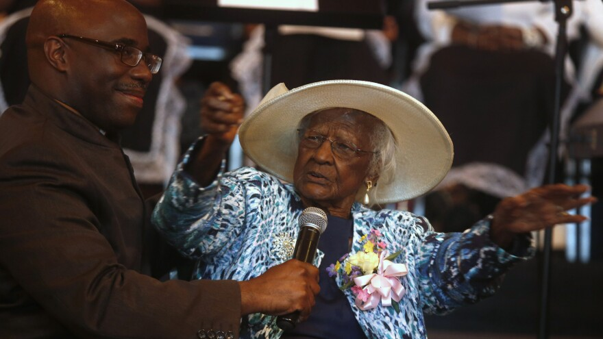 Jeralean Talley addresses the congregation as her pastor, Reverend Dana Darby, holds the microphone for her during a celebration of her 115th birthday.