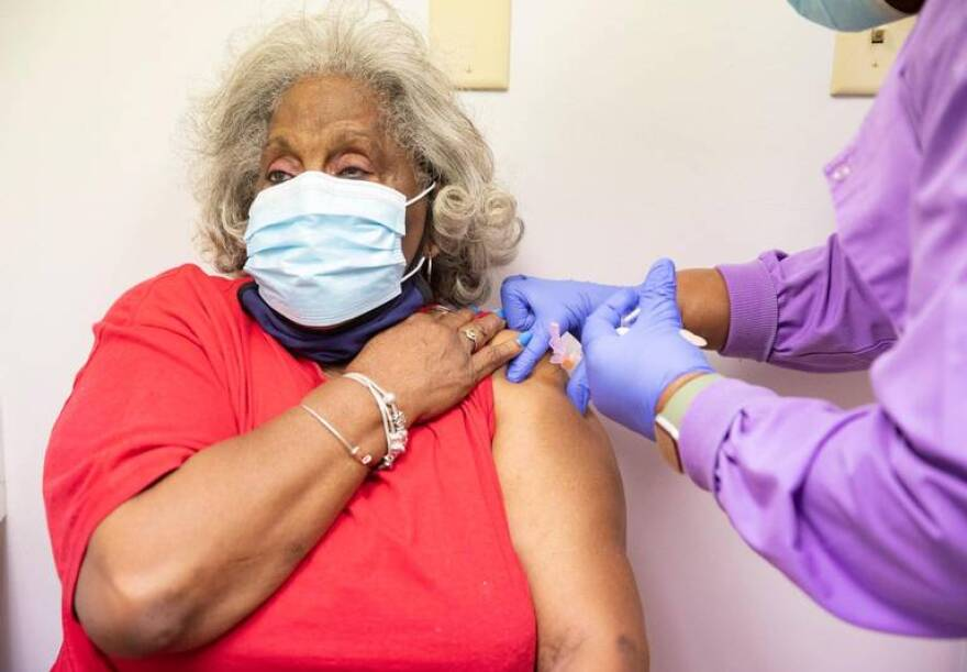 A woman receives a vaccine for coroanvirus