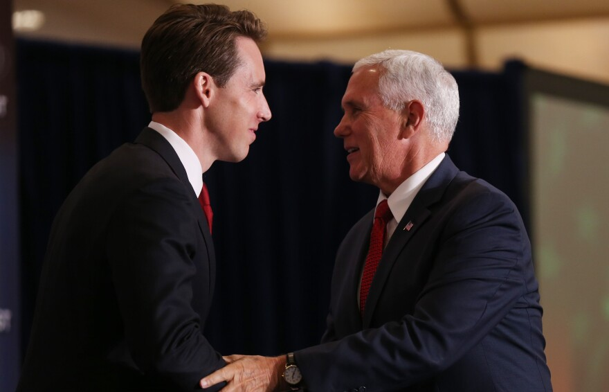 Attorney General Josh Hawley shakes hands on Thursday with Vice President Mike Pence. Pence made a speech in downtown St. Louis to bolster President Donald Trump's policies.