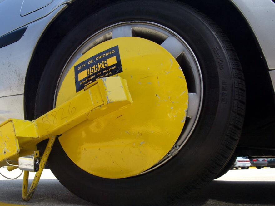 """A """"Denver Boot"""" wheel lock attached to a car in a parking lot at O'Hare International Airport in Chicago."""