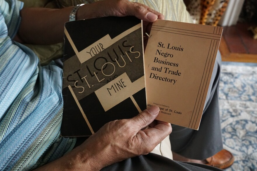 John Wright holds two black business and travel guides. The 1934 issue of the 'St. Louis Negro Business and Trade Directory' featured all-black companies, while 'Your St. Louis and Mine' included white-owned businesses that welcomed black patrons.