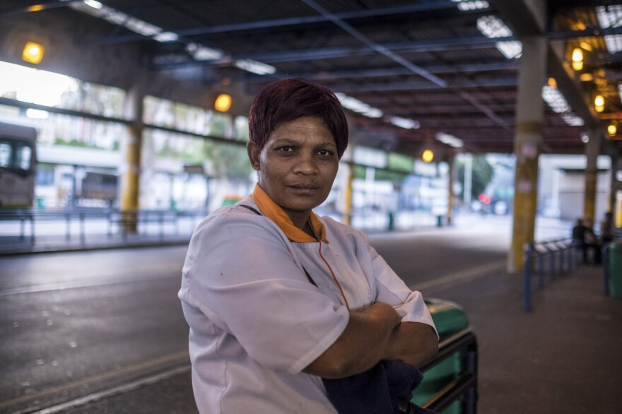 Anna Simpson, 41, who works in the kitchen of a Cape Town hospital, waits for a bus to take her home to the community called Lost City, where she lives with her husband. Many workers who keep crucial industries running live in townships and rely on public transport to get to work — putting them at risk of exposure to COVID-19.