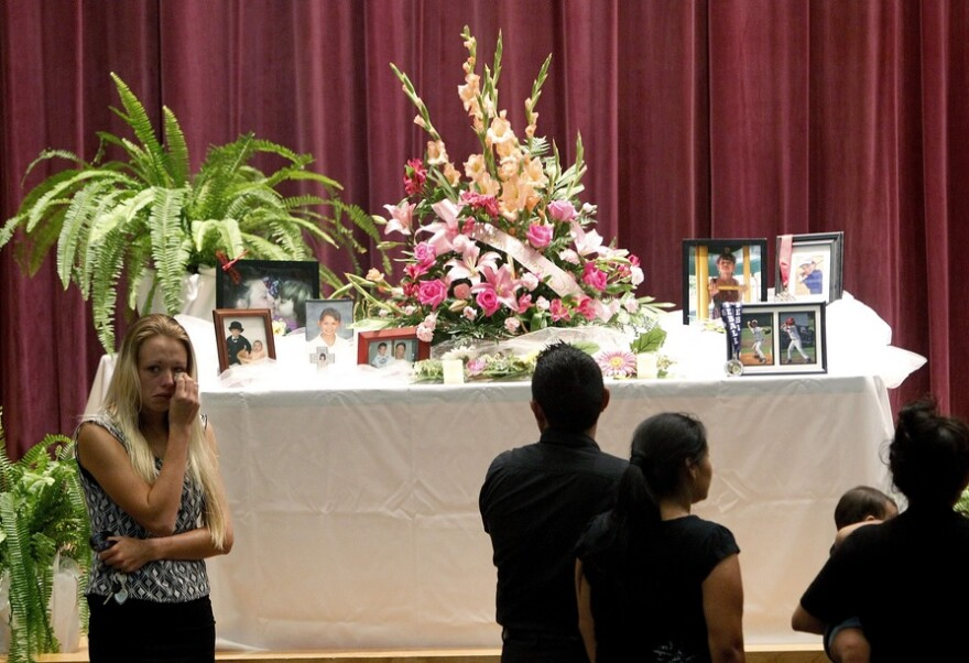 Mourners look at a display of photos during a memorial service at Bell High School for the victims of Thursday's shootings on Sunday, Sept. 21, 2014 in Bell, Fla.