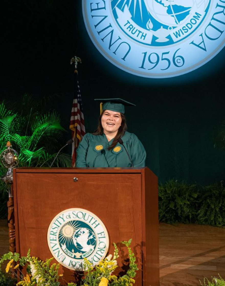 Young woman in cap and gown stands at podium