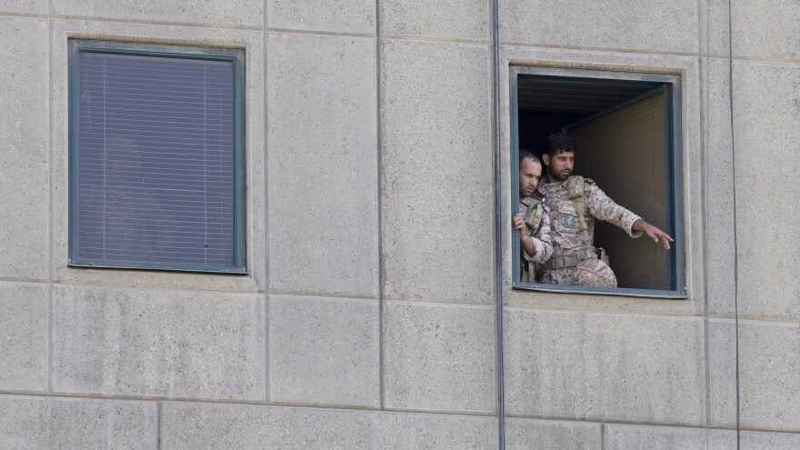 Men in military uniform stand at a window in the Iranian Parliament building following an attack on Wednesday in Tehran. More than a dozen people were killed and many more wounded during twin gun and suicide bomb attacks in Iran's capital.