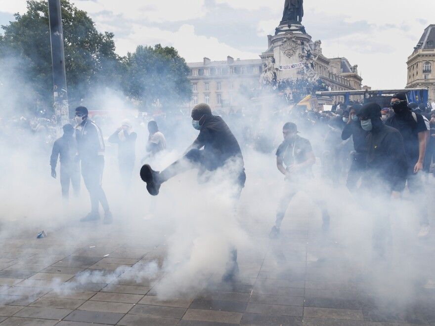 A man kicks a tear gas canister during a march against police brutality and racism in Paris.