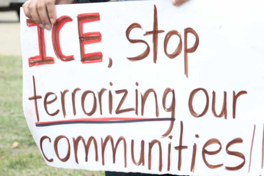 Demonstrators with signs gathered outside CVE Technology in Allen during the ICE raid.