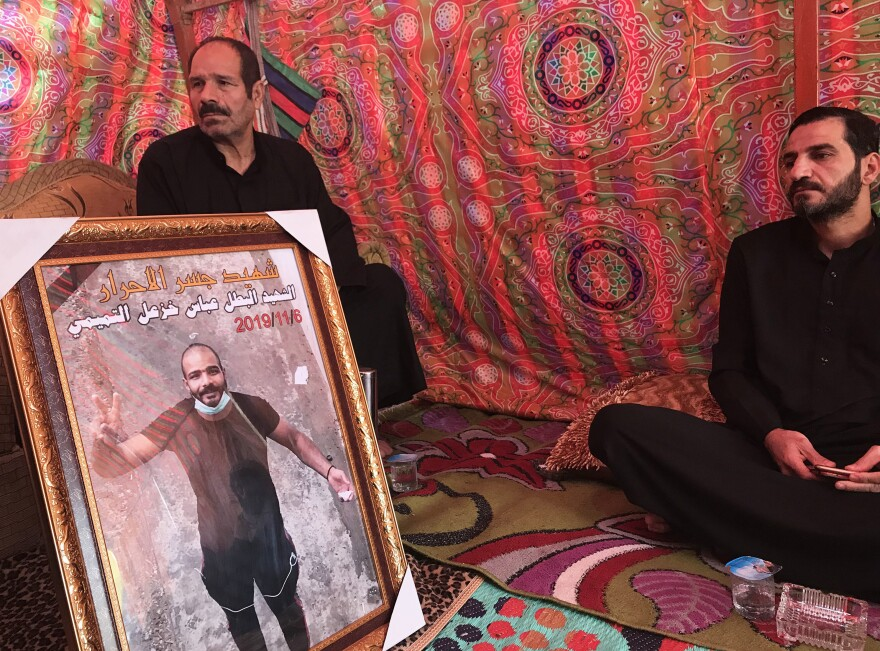 Mourners sit with a framed photo of Abbas Salih, who was shot dead Nov. 6.