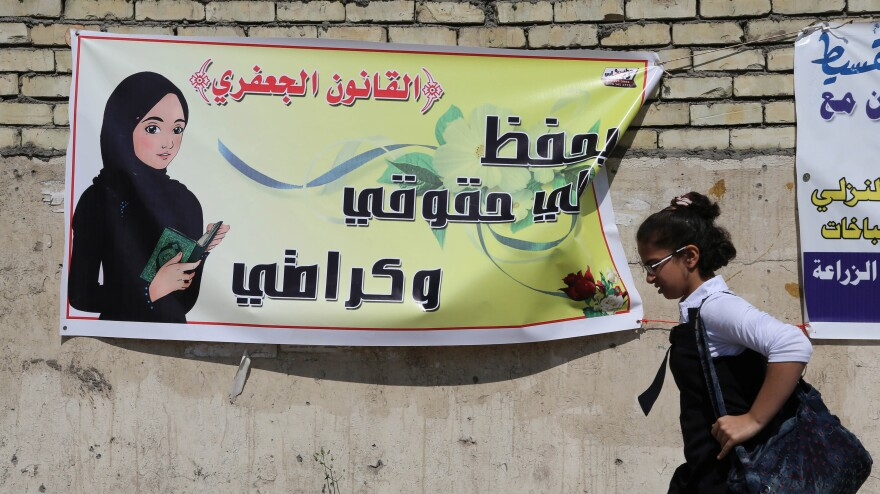 "An Iraqi schoolgirl passes a banner supporting a proposal that, among other things, would allow men to marry girls as young as 9. Opponents say it would mark a major setback for women and children. The Arabic on the banner reads: ""The Jaafari Personal Status Law saves my rights and my dignity."""
