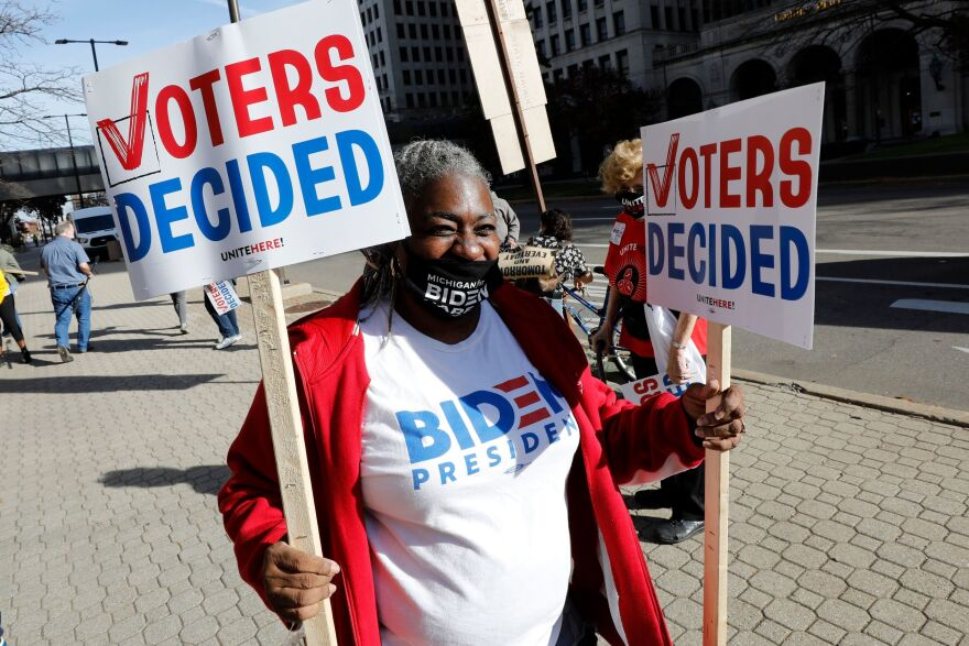 Zinnia Patcas hands out signs in Detroit on Nov. 7 as people gather to celebrate Joe Biden's win in the presidential election.