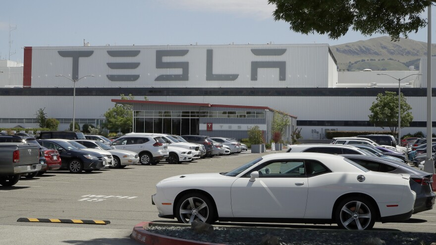 Vehicles are seen parked at the Tesla car plant in Fremont, Calif., on Monday. The parking lot was nearly full; Tesla resumed production in defiance of an order from county health authorities.