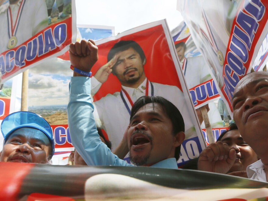 Johnny Dagami, Jr., an impersonator of Filipino boxer Manny Pacquiao, joins other supporters in Manila while Pacquiao files his certificate of candidacy as a senatorial candidate in next year's elections.