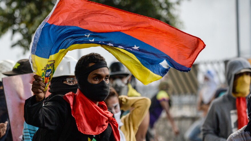 An anti-Maduro demonstrator waves the Venezuelan flag at a protest in the capital, Caracas, on Wednesday. The government banned such demonstrations nationwide for the next five days, as the country approaches a Sunday vote on delegates for Maduro's constituent assembly, which would lead a rewrite of the constitution.