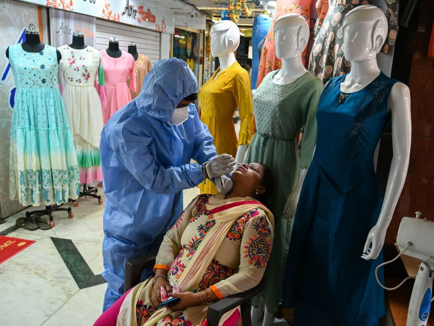 A health worker wearing protective gear collects a swab sample from a woman during a medical screening for the Covid-19 coronavirus at a garment wholesale market in Mumbai, India, on Friday.
