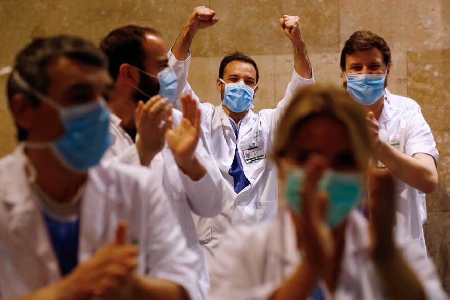 """Healthcare workers dealing with the new coronavirus crisis in Spain, applaud in return as they are cheered on by people outside """"El Clinic"""" University Hospital in Barcelona on March 26, 2020.  (PAU BARRENA/AFP via Getty Images)"""