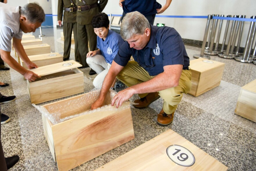 U.S. Defense Department forensic anthropologists in Wonsan, North Korea examine the contents of boxes containing the possible remains of U.S. MIAs July 27, 2018.