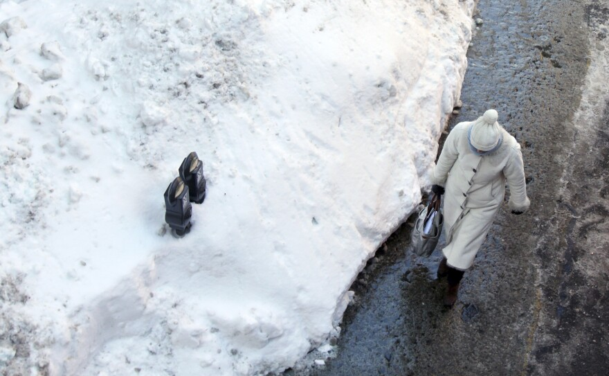 Parking meters sits mostly buried in a mound of snow on Friday in downtown Boston.