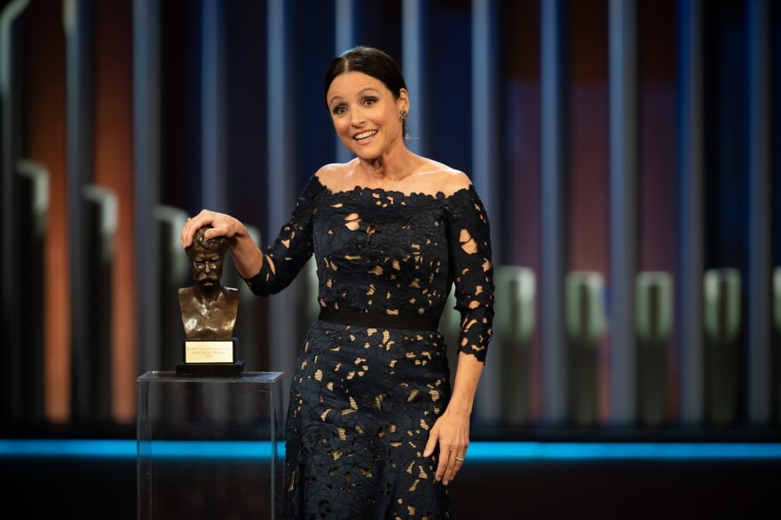 Julia Louis-Dreyfus poses with a bust of Mark Twain, upon receiving the Mark Twain Prize for American Humor at the Kennedy Center in Washington, D.C.