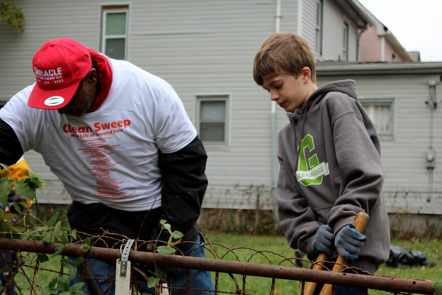 University City councilman Rod Jennings and Lucas Hayden, 10, use brush cutters to remove overgrown plants from a fence during a neighborhood cleanup event Oct. 28, 2017.