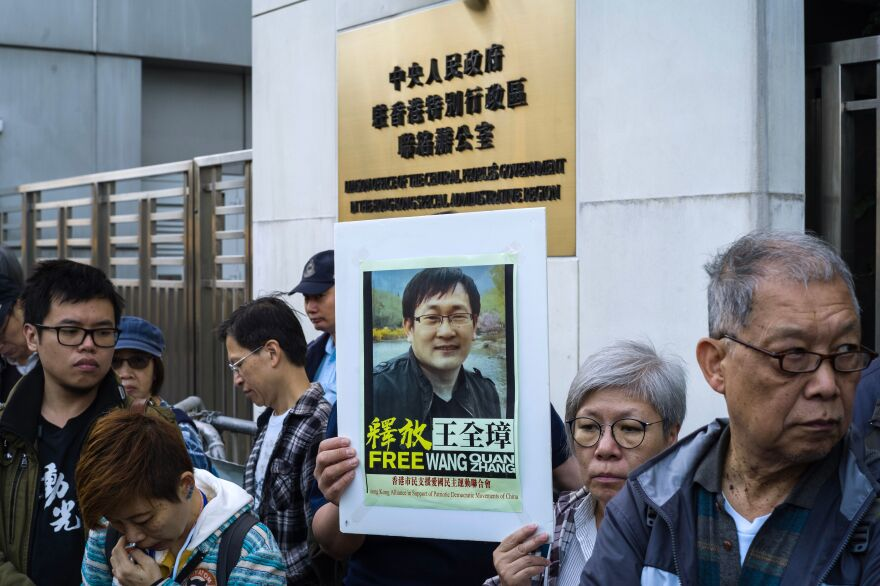 Activists hold a sign showing detained Chinese human rights lawyer Wang Quanzhang at a rally outside the Chinese Liaison Office in Hong Kong on Dec. 26, 2018, as Wang's trial was set to begin in China.