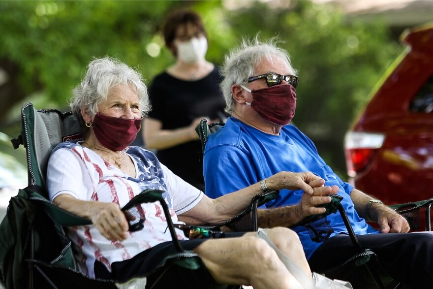 Neighbors wearing face masks listen from lawn chairs to the free concert on Saturday.