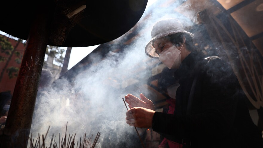 A worshiper burns incense during a Birthday of Buddha service to pray for overcoming the coronavirus pandemic at Jogyesa Temple in Seoul on Thursday.