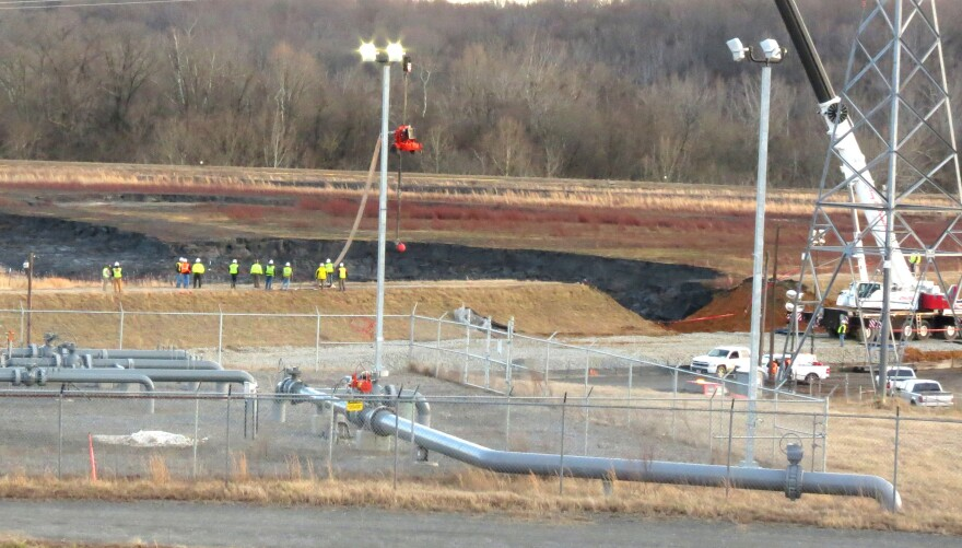Duke Energy crews work to repair the broken coal ash pond. Coal ash is a byproduct of the coal burned to produce electricity.