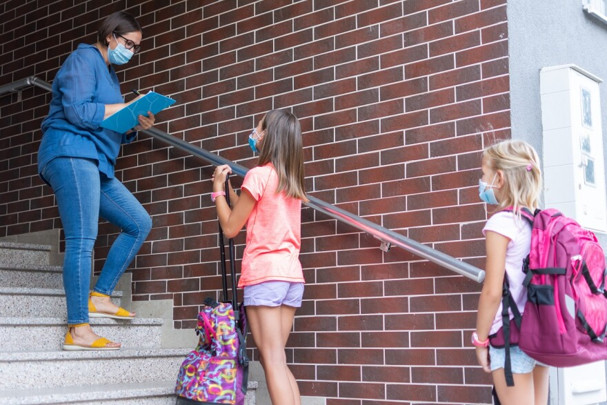 Teacher with face mask welcoming children back at school after lockdown.